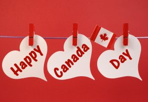 Happy Canada Day message greeting with the Canadian maple leaf flag hanging from pegs on a line against a red background, for July 1 holiday.